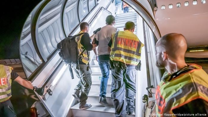 Michael Kappeler/dpa/picture allianceماموران پولیس آلمان یک مهاجر افغان را به درون هواپیمایی هدایت می کنند تا به افغانستان اخراج شود.