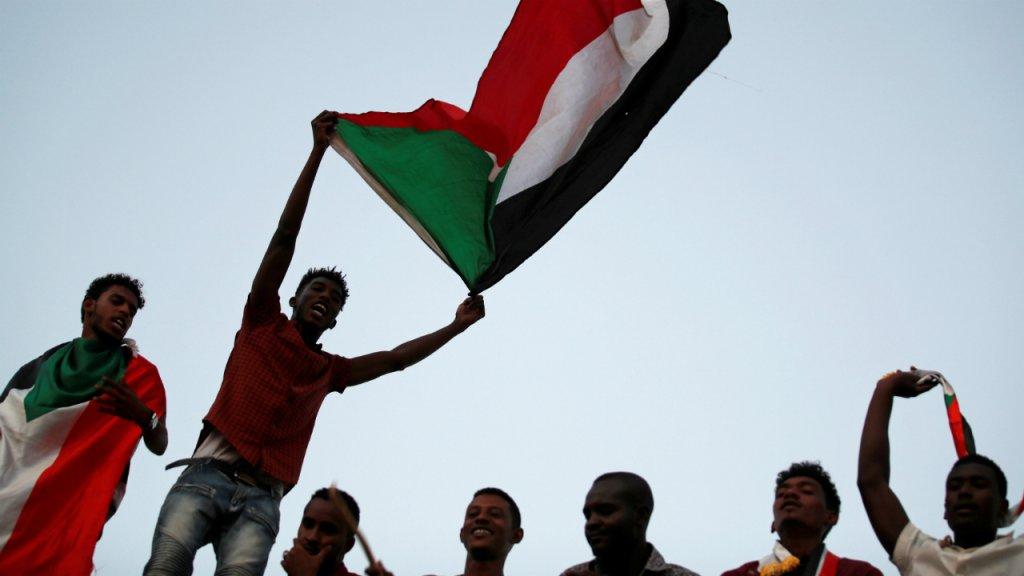 Des Soudanais agitent le drapeau national lors d'une manifestation en face du ministère de la Défense à Khartoum, le 21 avril 2019. Crédit : Umit Bektas / Reuters