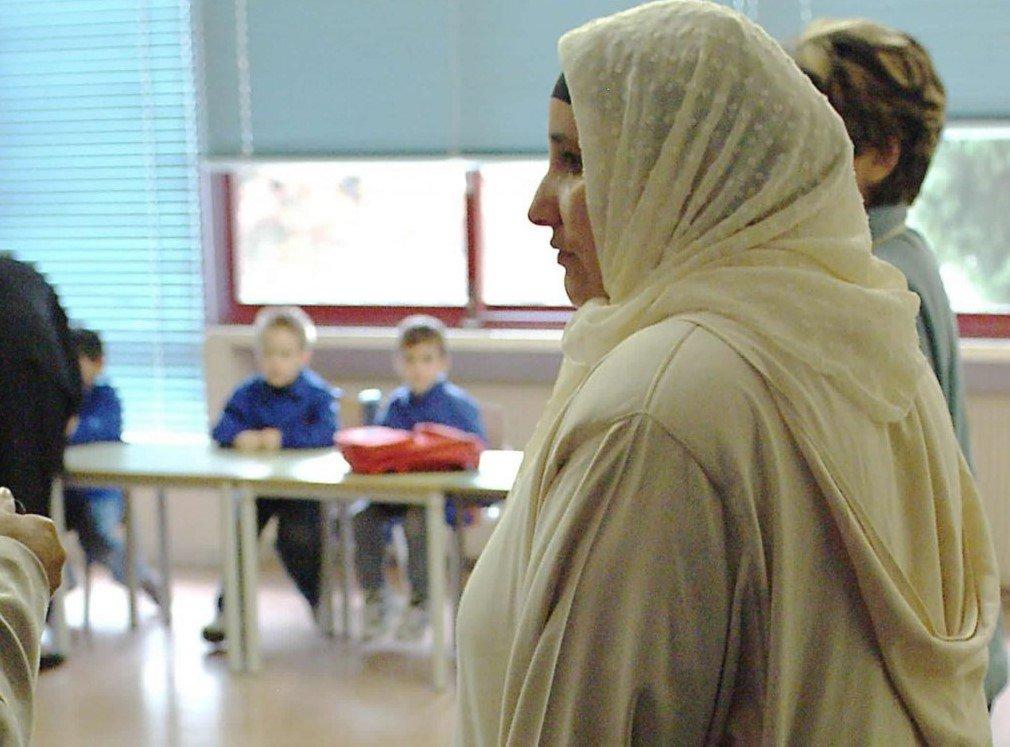 امرأة مع طفلها داخل المدرسة الابتدائية في فولينا بمقاطعة تريفيزو الإيطالية. المصدر: أنسا.