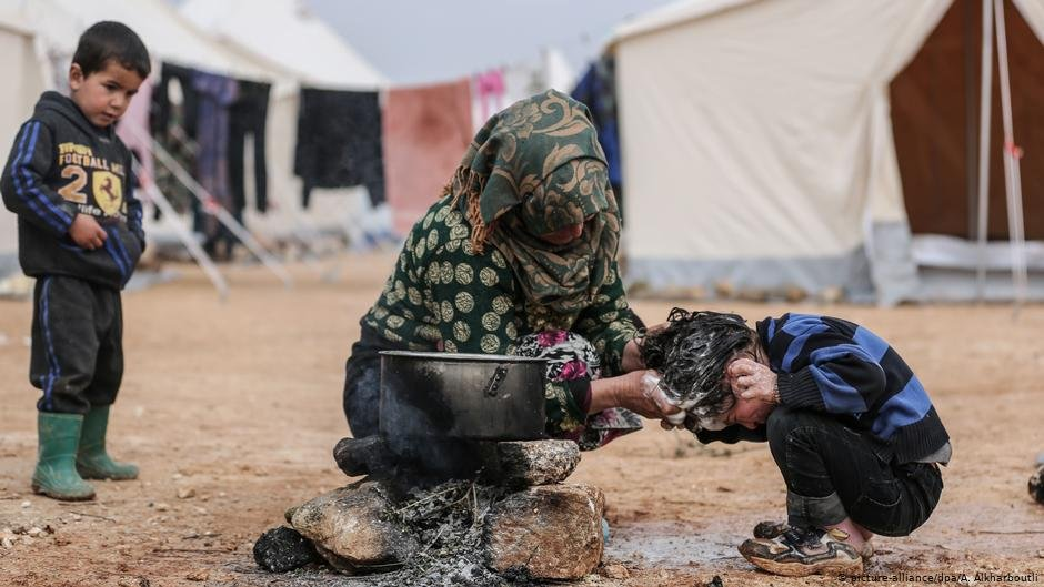 A woman washes the hair of a child in Syria | Photo: Picture-alliance/dpa