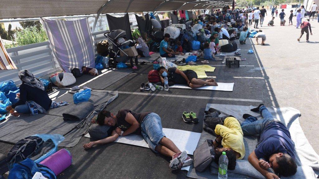 گروهی از مهاجرانی که از کمپ ویران شده  موریا فرار کردهاند، در پارکینگ مغازه لیدل در امتداد جاده میتلین زندگی میکنند. عکس از مهدی شبیل/  مهاجر نیوز
