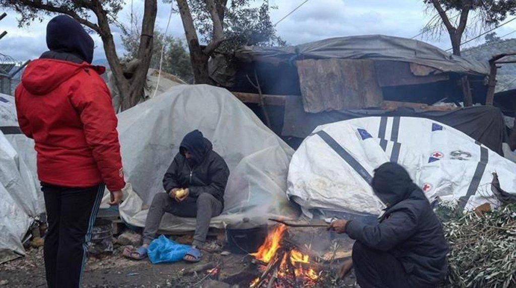 مهاجرون يتجمعون حول النار للتدفئة في بساتين الزيتون حول مخيم موريا. المصدر: صحيفة بيجي.