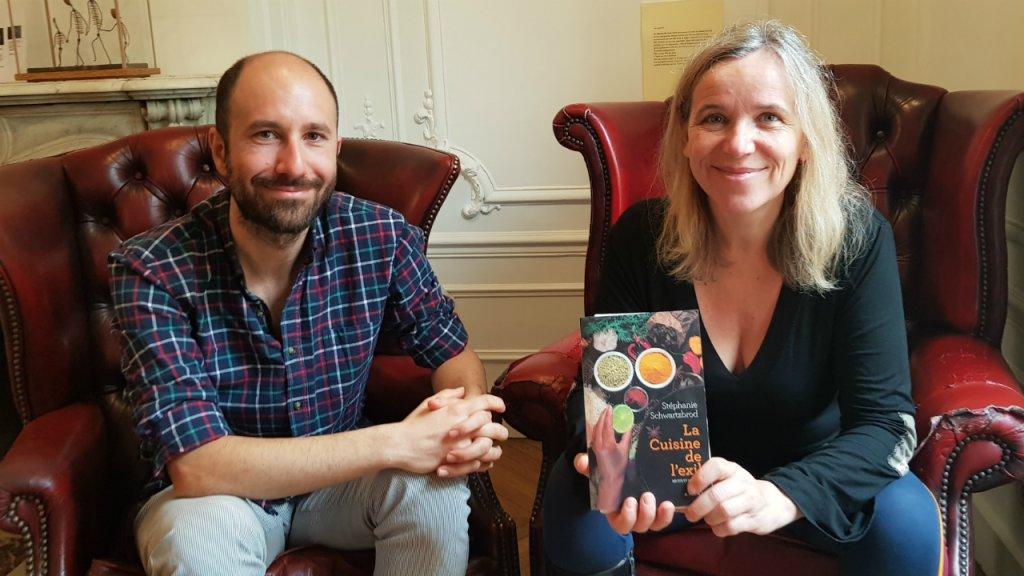 """Stéphanie Schwartzbrod, auteur de """"La Cuisine en Exil"""", accompagnée de Saeed Mirzaei, un Iranien installé en France. Crédit : Anne-Diandra Louarn / InfoMigrants"""