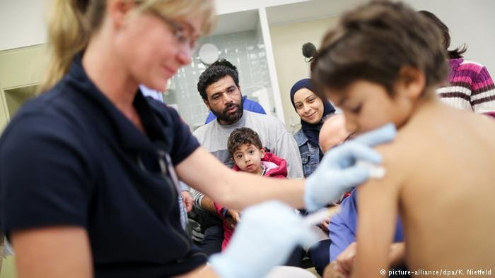 A refugee child gets a vaccine shot in Berlin
