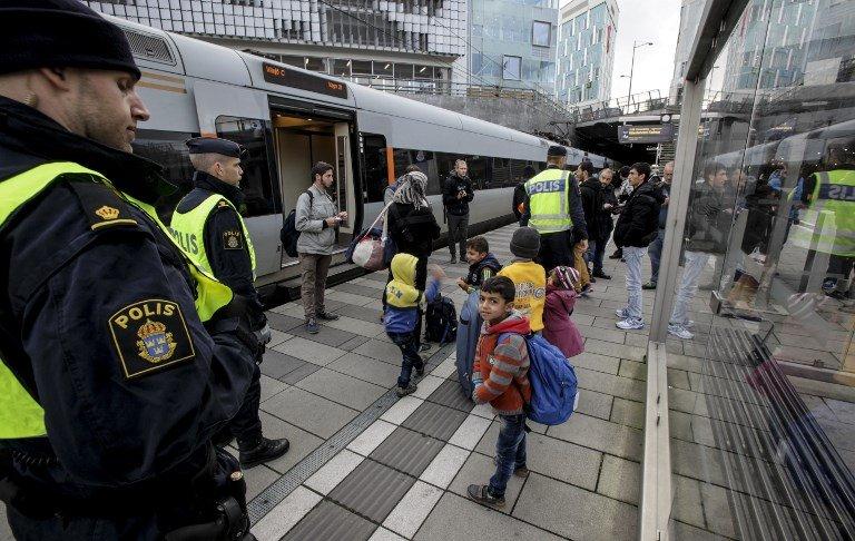 ©AFP/STIG-AKE JONSSON |Des policiers et un groupe de migrants se tiennent sur la plate-forme à l'extrémité suédoise du pont entre la Suède et le Danemark à Malmö, en Suède, le 12 novembre 2015. (Photo d'illustration)