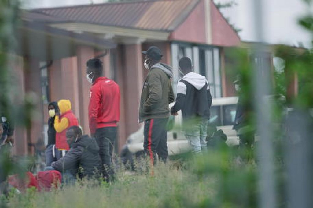 ANSA / مهاجرون يرتدون أقنعة أمام مركز استقبال في إيطاليا. المصدر: أنسا.