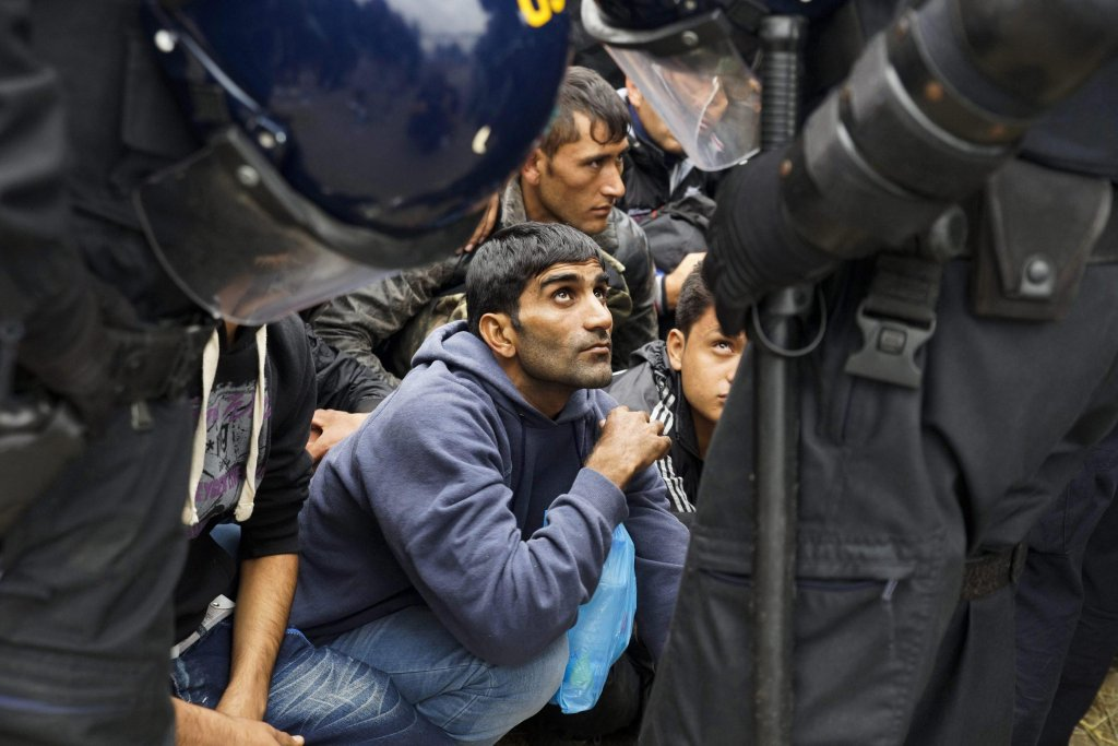 Migrants wait in front of Croatian police officers near the entrance of a reception center close to Croatia's border with Serbia, in Opatovac, Croatia, 22 September 2015. EPA/ZOLTAN BALOGH HUNGARY