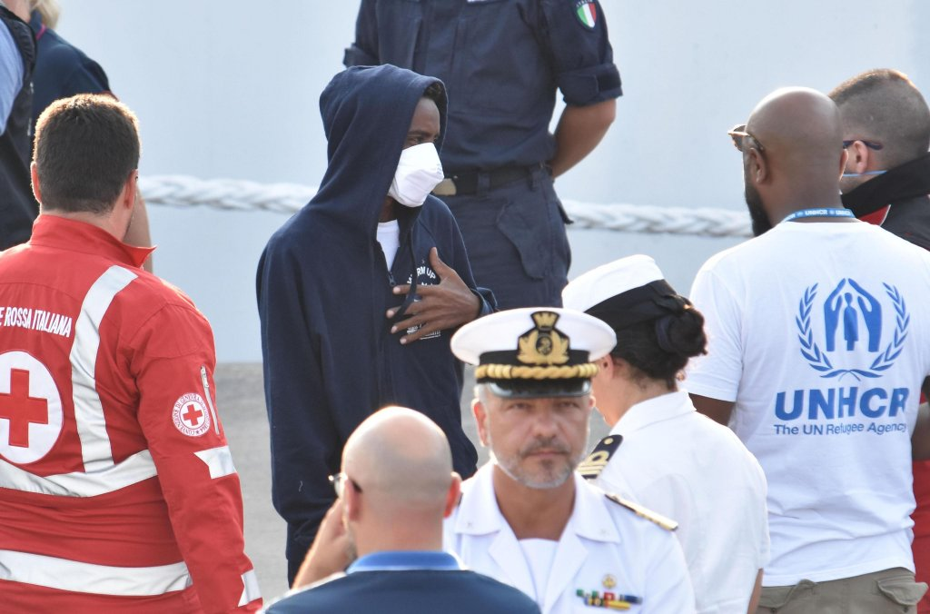 """ANSA / مهاجرون إريتريون يهبطون من سفينة حرس السواحل الإيطالية """"ديتشيوتي"""" في ميناء كاتانيا الإيطالي. المصدر: أنسا/ أوريتا سكاردينو."""