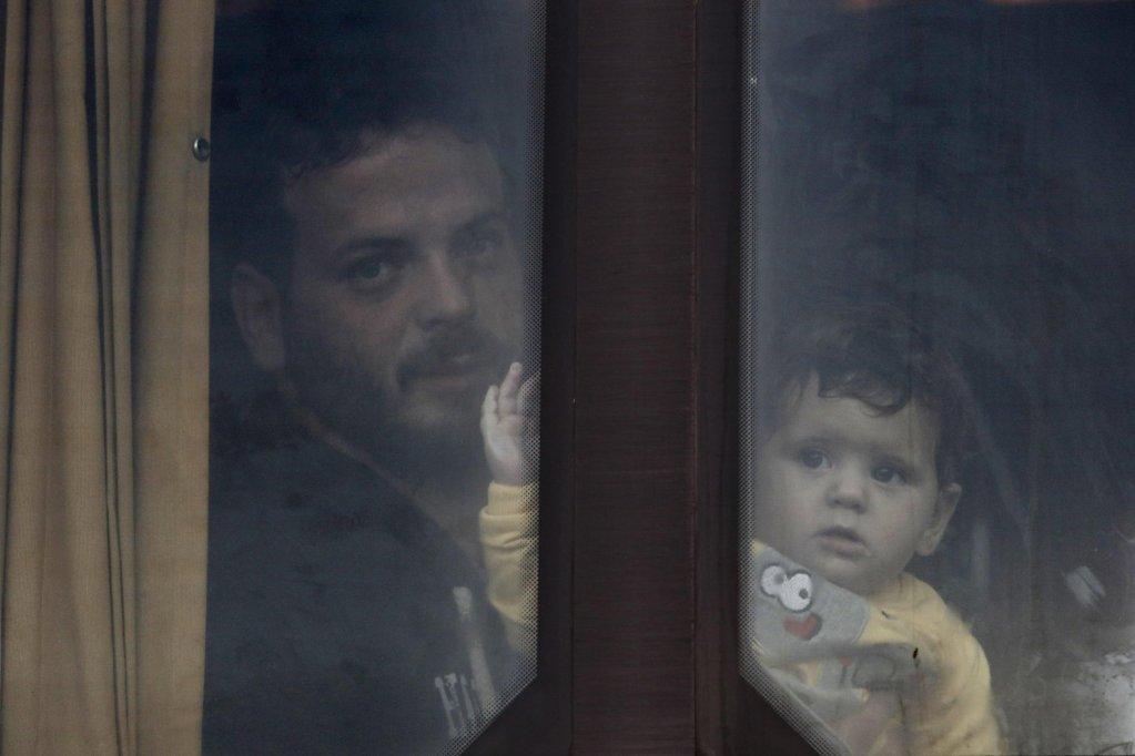 """ANSA / لاجئ يحمل طفله داخل حافلة، وينتظر نقله إلى مركز الاستضافة، بعد وصوله على متن السفينة """"بلو ستار 2"""" لميناء بيريوس بالقرب من أثينا. المصدر: إي بي إيه/ يانيس كوليسيدس."""
