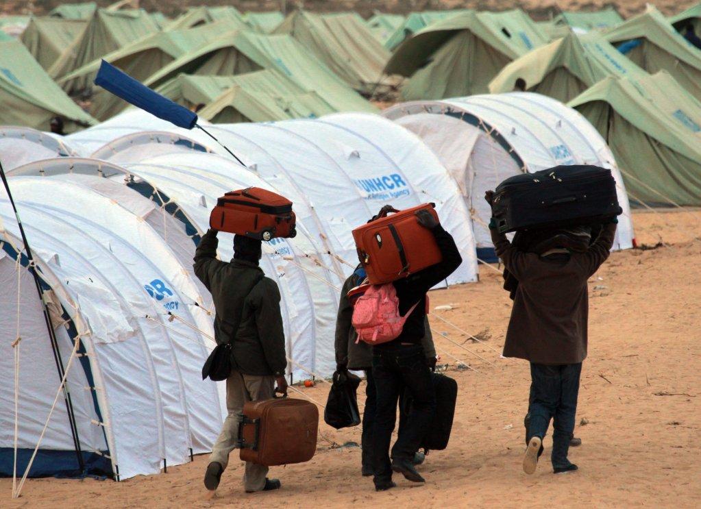 """ansa / مهاجرون هربوا من النزاع في ليبيا يحملون أمتعتهم في خيمة تابعة للمفوضية العليا للاجئين في مخيم بالقرب من معبر رأس جدير في تونس. المصدر: """"إي بي إيه""""/ جيم هولاندر."""