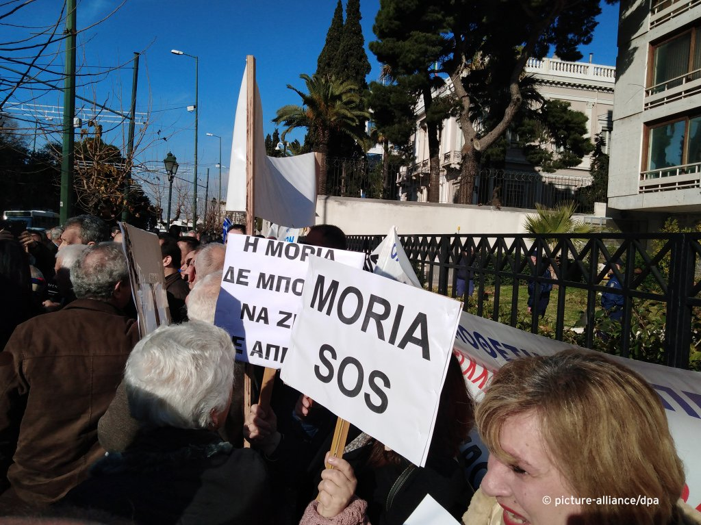 "Protester holding sign reading ""Moria SOS"" - hundreds of islanders demonstrated out of protest against the construction of new migrant camps on the Greek Aegean islands on February 13, 2020 
