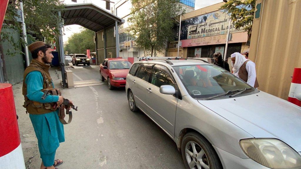 أعضاء حركة طالبان يفتشون السيارات في مدخل المنطقة الخضراء، حيث توجد معظم السفارات في كابول. المصدر: إي بي إيه