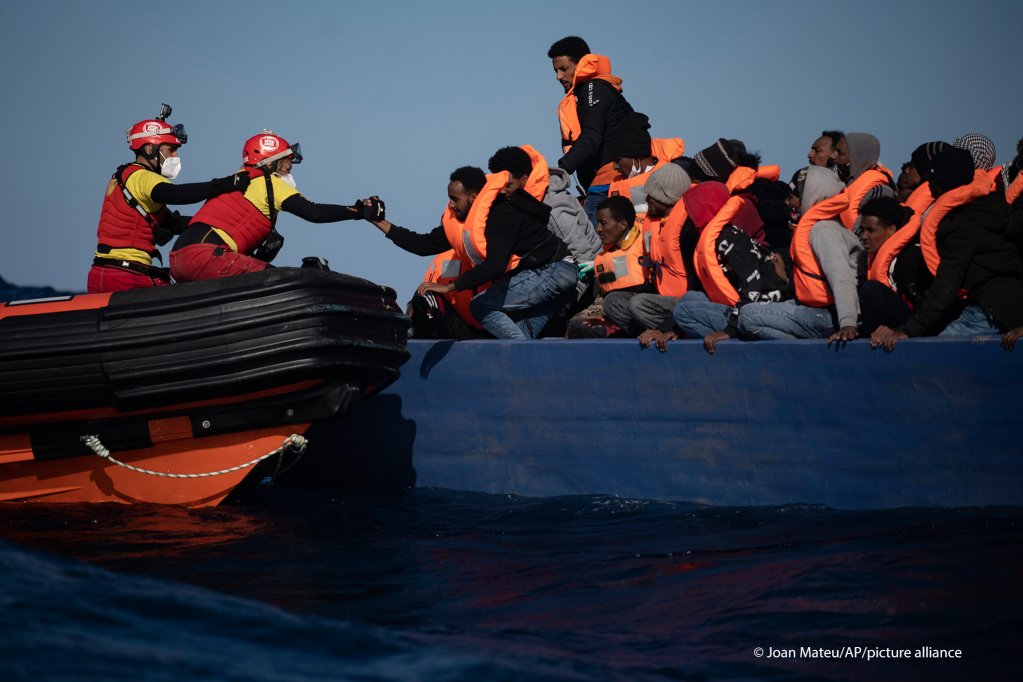 Migrants from Eritrea, Egypt, Syria and Sudan are assisted by aid workers of the Spanish NGO Open Arms, after fleeing Libya on board a wooden boat in the Mediterranean Sea on January 2, 2021 | Joan Mateu/AP Photo