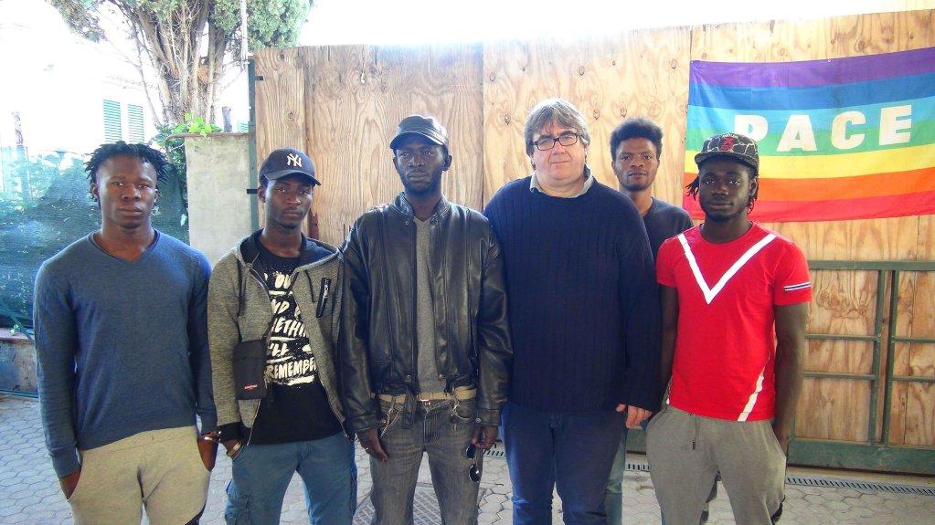 الأب ماسيمو بيانكالاني (الثالث من اليمين) مع عدد من المهاجرين. المصدر: أنسا.