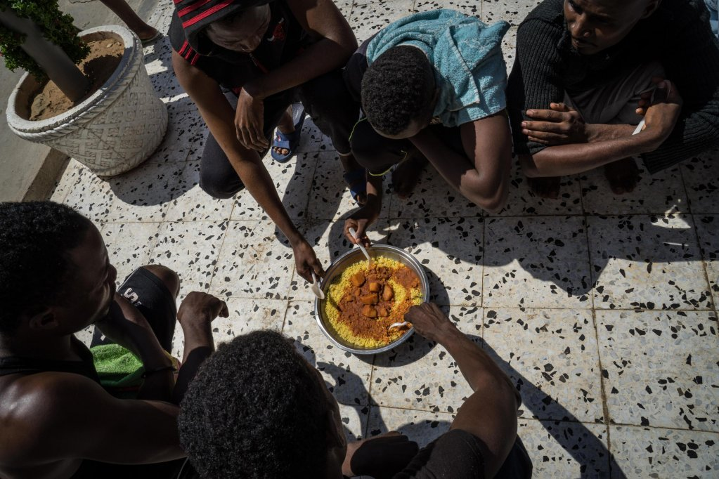 Migrants having a meal at the Janzour detention center, south-west of Tripoli | Credit: Zuhair Abusrewil