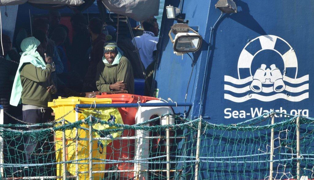 """ANSA /  مهاجرون يحتفلون على متن سفينة الإنقاذ الألمانية غير الحكومية """"سي ووتش 3"""" برسوها في ميناء كاتانيا الإيطالي. المصدر: أنسا/ أورييتا سكاردينو."""