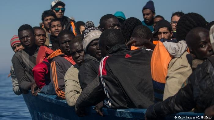 Migrants and refugees wait to be rescued from an overcrowded boat off Lampedusa on May 18, 2017
