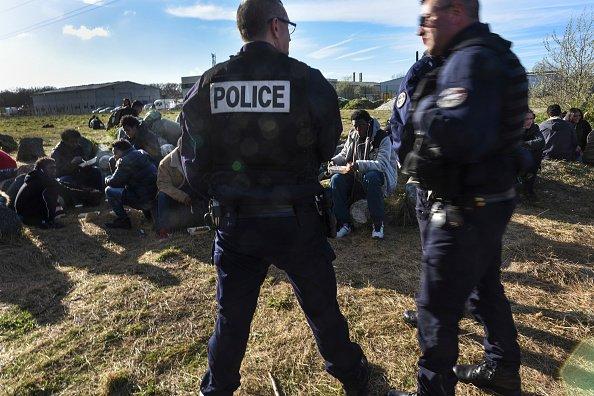 Image d'archives de policiers face à un groupe de migrants recevant des repas fournis par une ONG locale, à Calais, le 1er avril 2017. Crédit : Getty Images