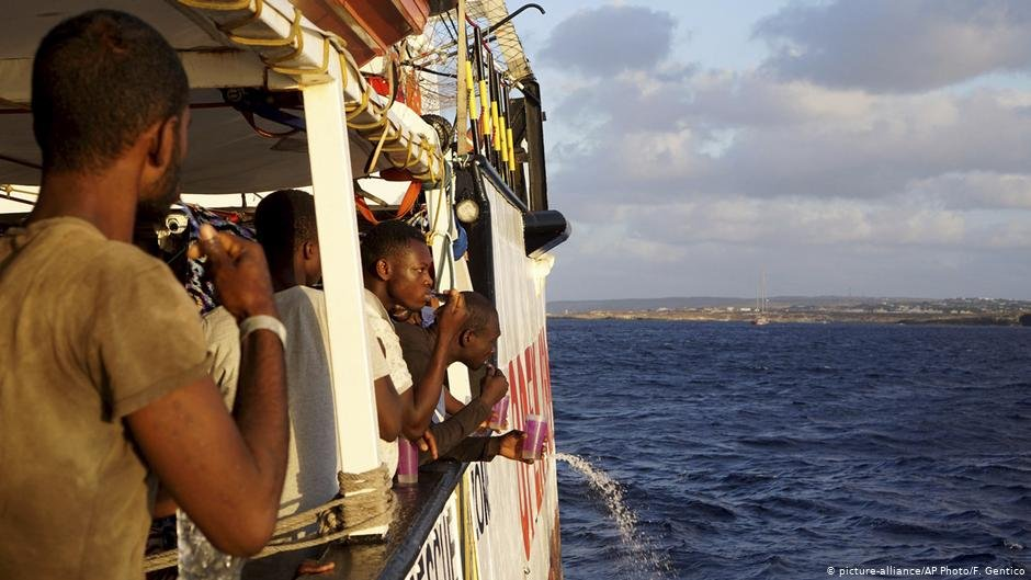 Migrants stand on board the rescue ship Open Arms as they approach Italy's Lampedusa island | Photo: Picture-alliance/AP Photo/F.Gentico