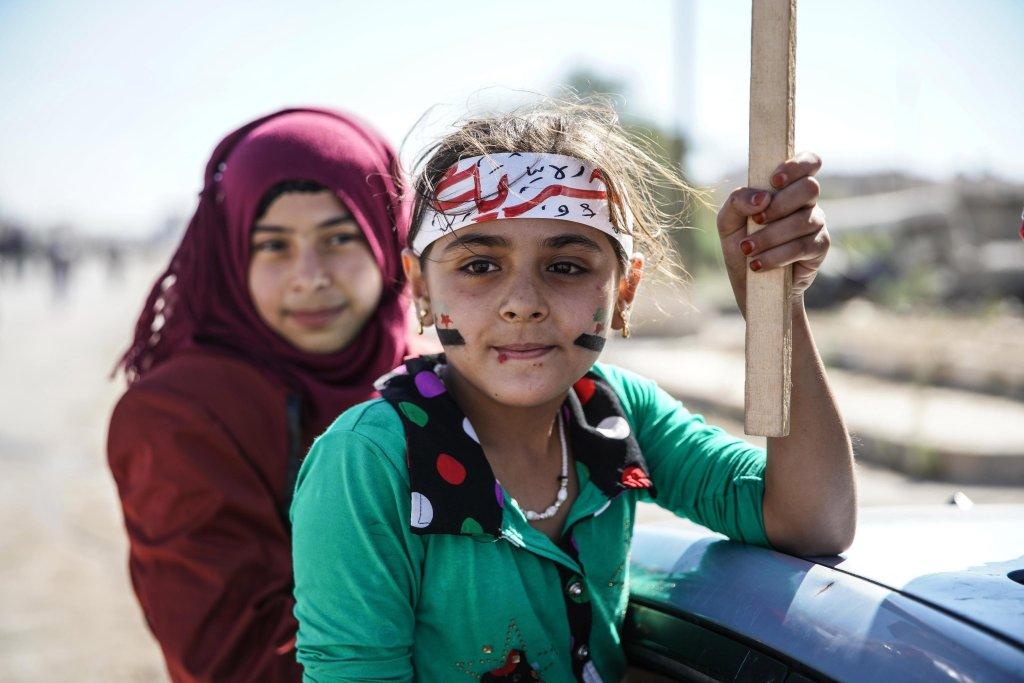 ANSA / أطفال يحملون علم الثورة السورية ولافتات خلال احتجاج في كفر نابل بمدينة معرة النعمان، معقل المتمردين في محافظة إدلب السورية. المصدر: إي بي إيه.