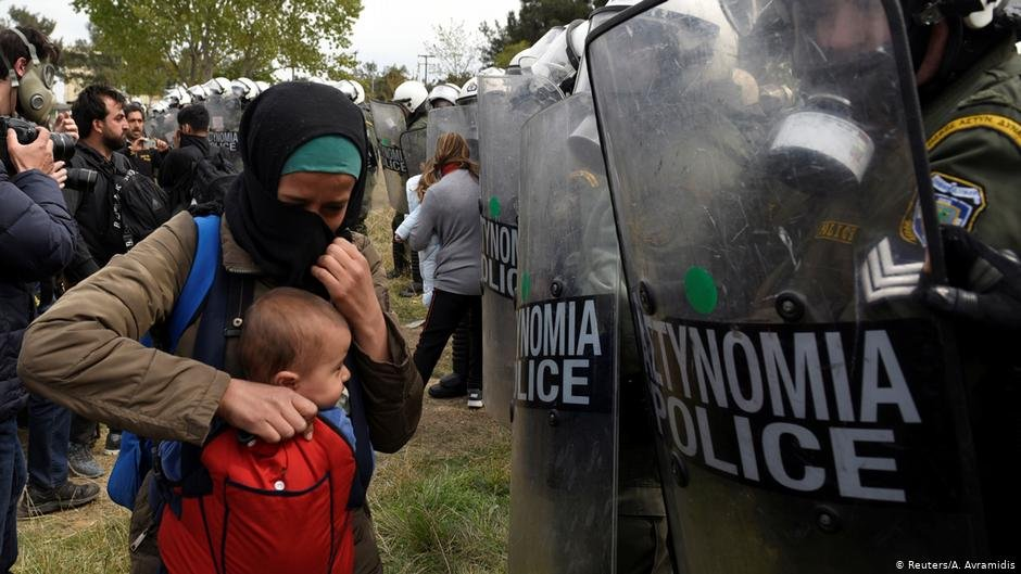 A refugee holds her child in front of Greek police in Diavata | Photo: Reuters/A.Avramidis