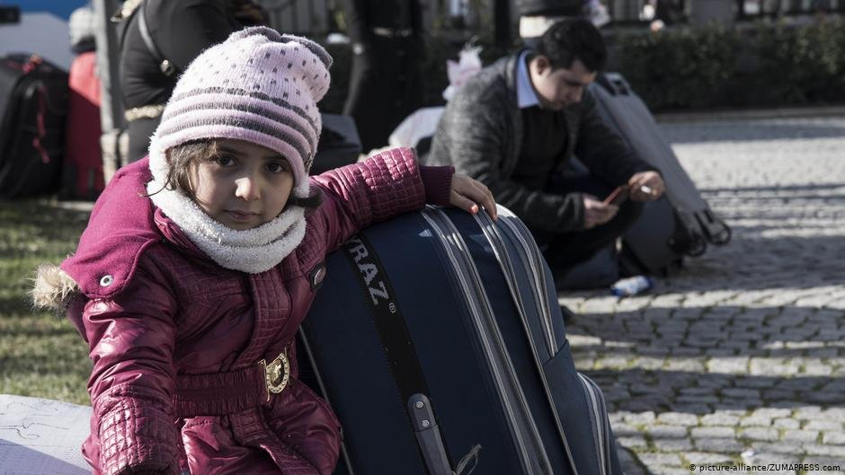 A Syrian child holds a suitcase as she and her family wait to be transported to Syria in January 2019 | Photo: Picture-alliance/ZUMAPRESS.com