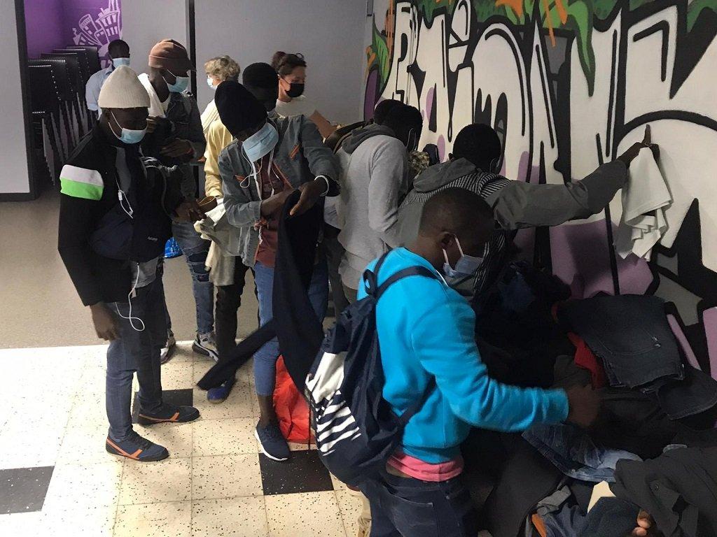 """مهاجرون يستلمون بعض الملابس خلال لقاء أسبوعي ينظمه متطوعو جمعية """"دياكيتي"""" في مركز """"غادشيتشي"""" الشبابي، في مدينة بايون جنوب فرنسا. المصدر/ مهاجر نيوز"""