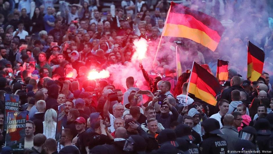 Demonstrators in Chemnitz hold up German flags and release fire during a right-wing protest against foreigners in Germany | Photo: Picture-alliance/dpa/J.Woitas