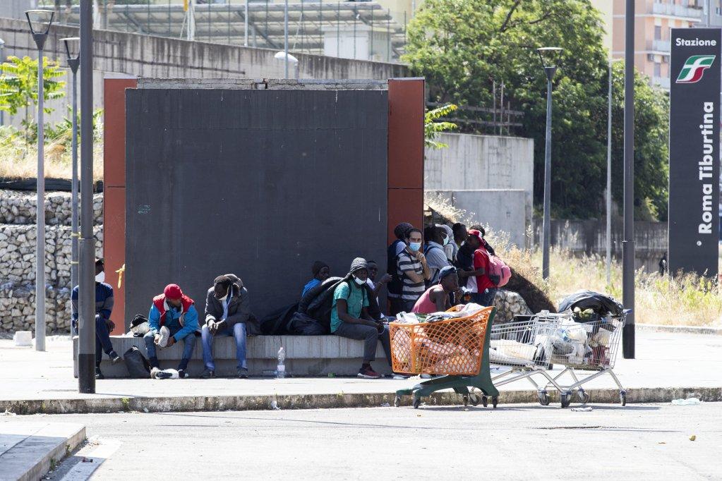 ansa مهاجرون يجلسون خارج محطة قطارات تيبورتينا في روما خلال انتظارهم متطوعي باوباب، الذين يقومون بتوزيع الطعام والمواد الأساسية. المصدر: أنسا.