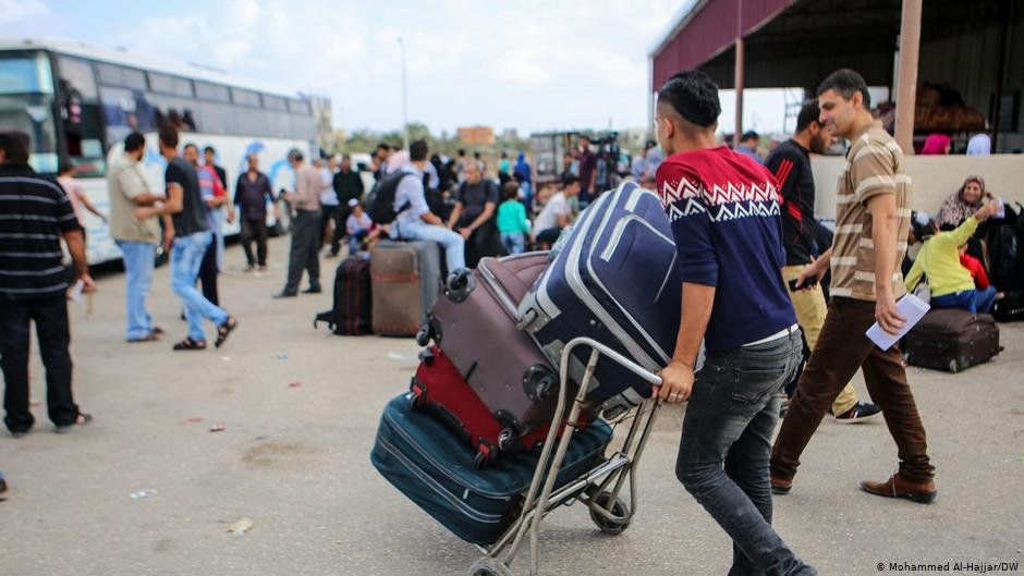 A young man wheels a trolley loaded with suitcases towards a busy bus station | Photo: Mohammed Al-Hajjar/DW