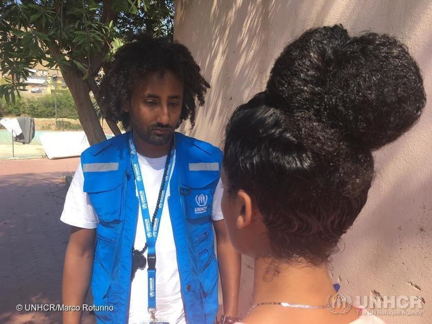 The photo taken from behind shows Feven, an Eritrean girl who reached Italy aboard the Open Arms after having spent 18 months in Libya, while she speaks to a UNHCR staff member   Photo: UNHCR/Marco Rotunno