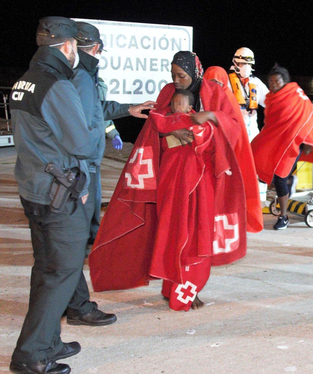 ANSA / مهاجرة وطفلها أمام عناصر الشرطة في ميناء موتريل في جنوب إسبانيا. أرشيف