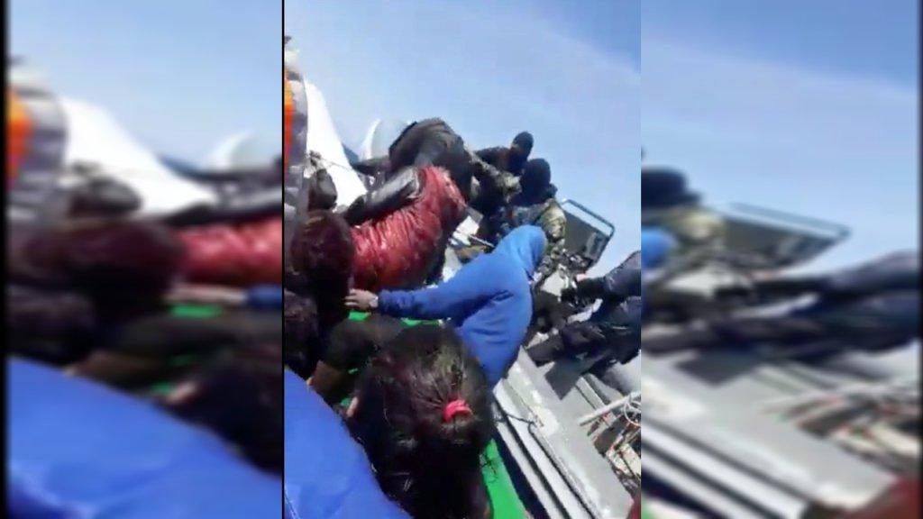 Des hommes masqués se sont approchés d'une embarcation de migrants en mer Égée. Crédit : Capture d'écran