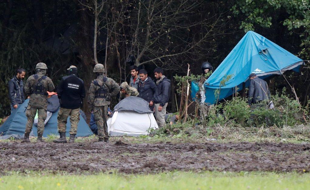 Des gardes-frontières polonais se tiennent à côté d'un groupe de migrants bloqués à la frontière entre la Biélorussie et la Pologne près du village d'Usnarz Gorny, en Pologne, le 1er septembre 2021. Crédit : Reuters