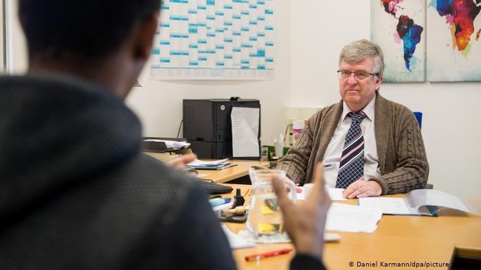 Daniel Karmann/dpa/picture alliance  طالب لجوء في ألمانيا يخضع للتحقق من هويته من هيئة الهجرة واللجوء (أرشيف)