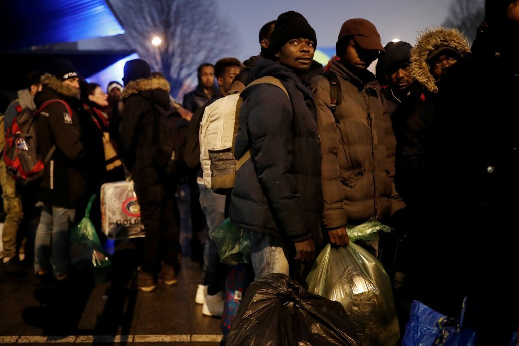 Migrants stand by as police dismantle a makeshift tent camp in northern Paris. Photo: Paris