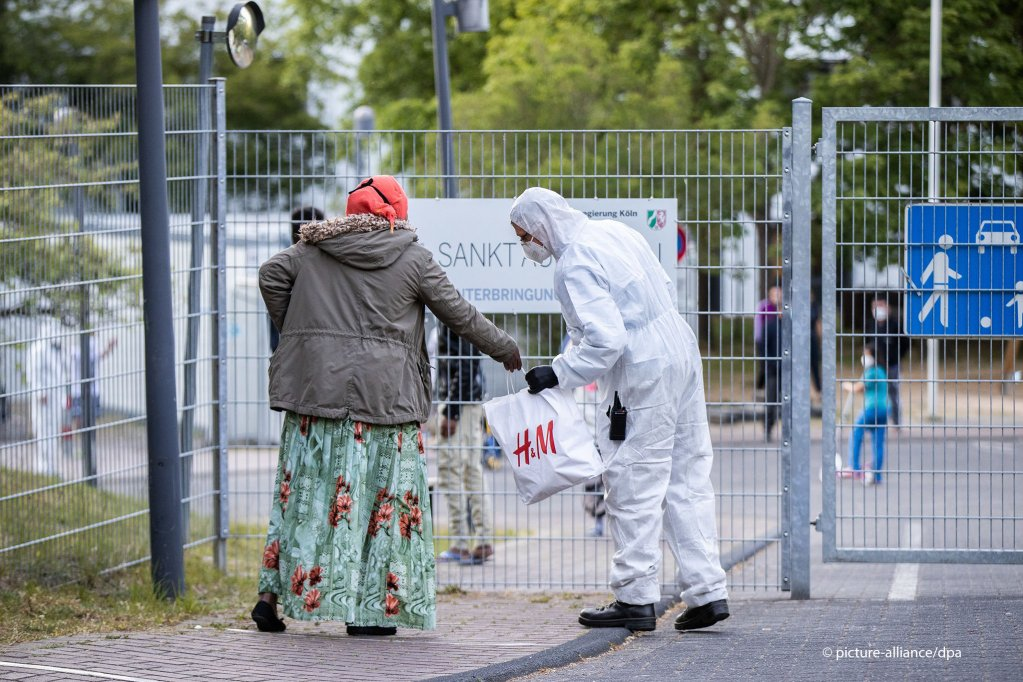 "An employee of a security service wearing a protective suit inspects the bag of a woman in front of the ""central accommodation facility"" (ZUE) St. Augustin near Bonn on May 18, 2020 