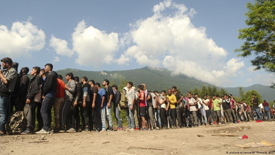 Migrants and refugees wait in line to receive supplies from the Red Cross at the Vucjak camp outside Bihac, Bosnia | Photo: Picture-alliance/AP Photo/A.Alic