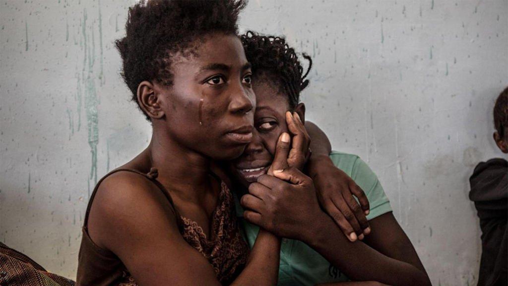 رويترز |مهاجرتان نيجيريتان تبكيان في ليبيا