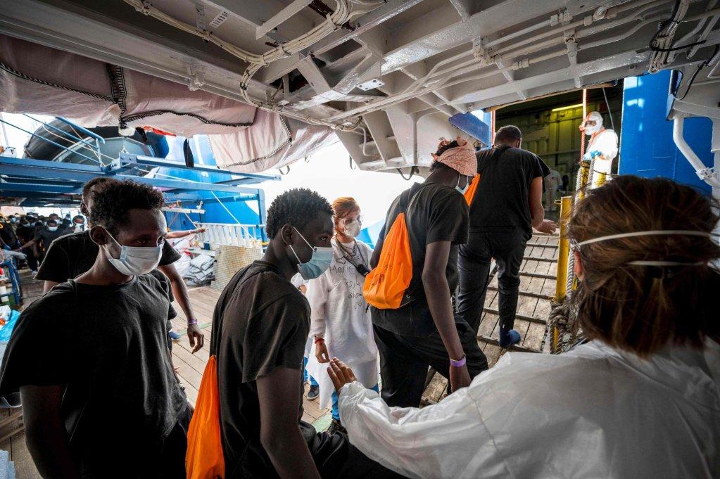 """مهاجرون ممن تم إنقاذهم يتلقون تحية أعضاء منظمة """"أطباء بلا حدود"""" في لامبيدوزا. المصدر: وكالة الأنباء الفرنسية/ توماس لوهانز."""