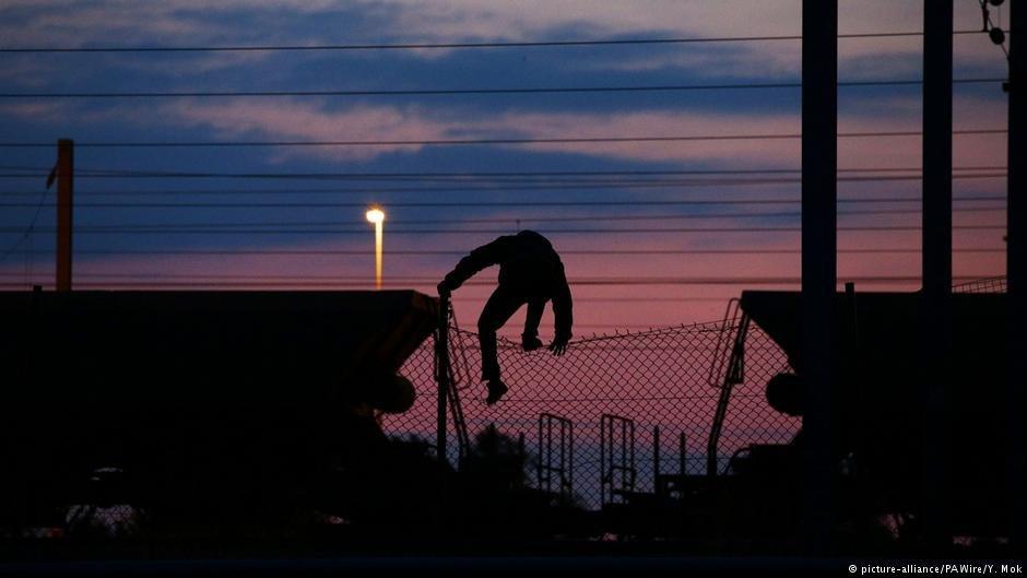 آرشیف: یک مهاجر در حال بالا رفتن از حصار فلزی نزدیک ایستگاه اروتونل در کاله. عکس از پیکچر الیانس
