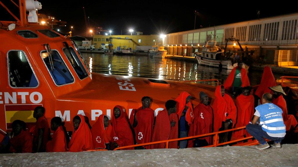 Un membre de l'agence européenne Frontex parle à des migrants en train de débarquer au port de Malaga après avoir été secourus en Méditerranée, le 2 septembre 2019. Crédit : Reuters