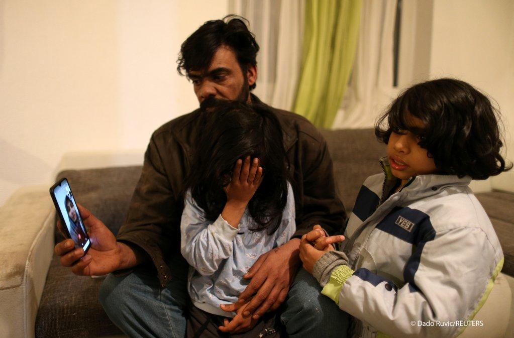 فرحان حزام من العراق وطفليه حسان وهوباس يتحدثون مع والدتهم الموجودة في ألمانيا، في منزل مؤقت في قرية بالقرب من فيليكا كلادوسا ، البوسنة والهرسك 30 يناير 2021.