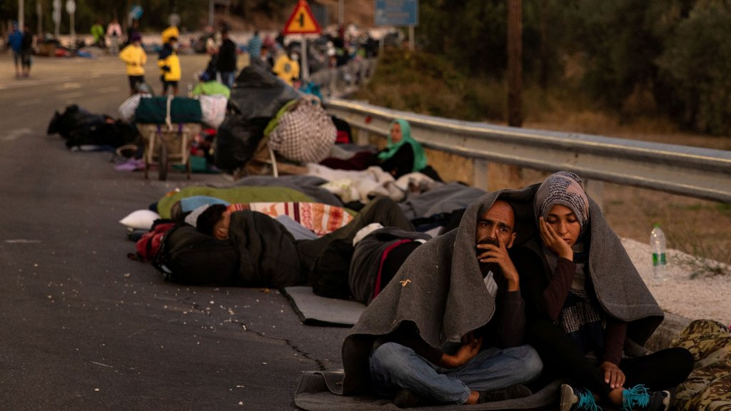 Un couple est assis dans la rue sous une couverture le 10 septembre 2020 après les incendie qui ont ravagé le camp de migrants de Moria, sur l'île grecque de Lesbos. Crédit : REUTERS/Alkis Konstantinidis