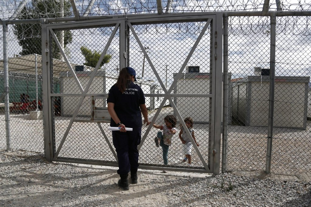 ANSA / ضابط شرطة يحرس أطفالاً عراقيين خلف سياج في مركز أميجداليزا لترحيل المهاجرين في أثينا. المصدر: إي بي إيه / يانيس كولسيديس.