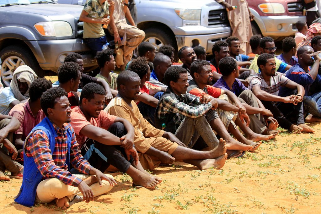 Men from Ethiopia, Sudan and Chad sit near the Libyan border prior to being arrested by RSF forces | Photo: Reuters