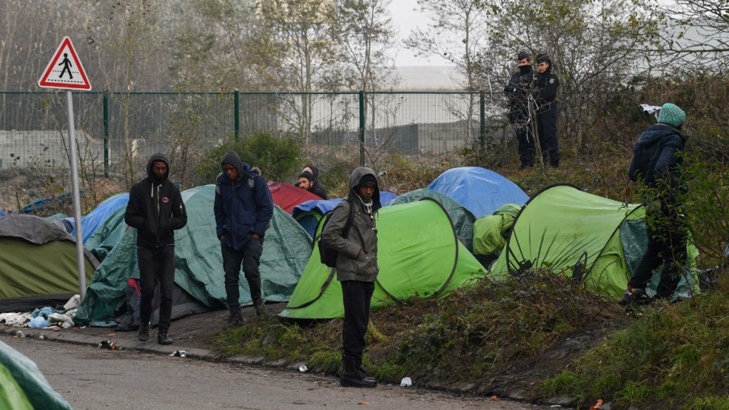 """Police officers dismantle migrants' tents in the """"rue des Huttes"""" camp in Calais, on October 31, 2019 