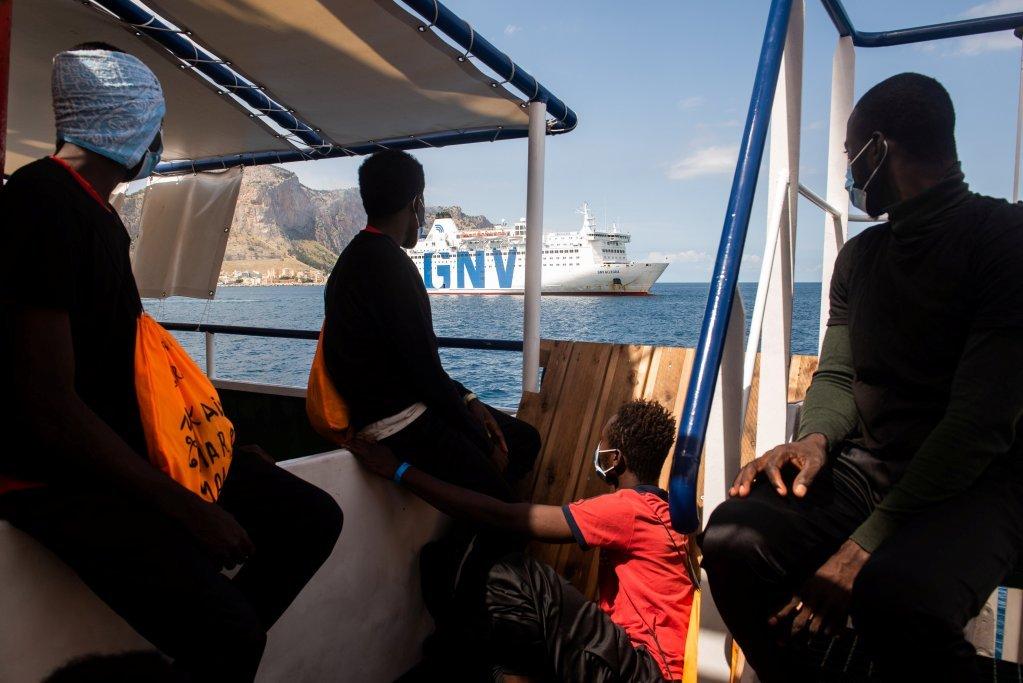 گروهی از مهاجران سی واچ ۴ در انتظار انتقال خود به کشتی ایتالیایی در بندر پالرمو هستند، ۲ سپتمبر ۲۰۲۰. عکس از رویترز