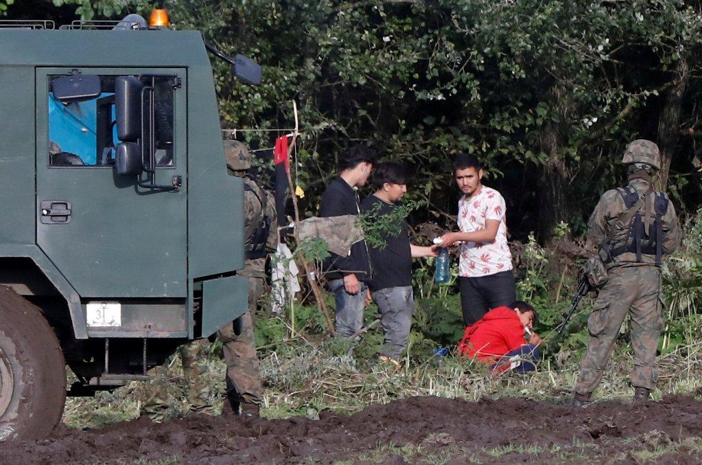 ضباط حرس الحدود البولنديون يقفون بجانب مجموعة من المهاجرين  بالقرب من قرية أوسنارز غورني. رويترز