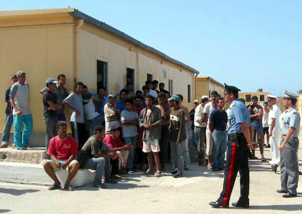 This photo shows dozens of migrants waiting in front of emergency shelters a at a Lampedusa first-level reception center Photo/ANSA/Archive